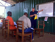 Crane & Safety explaining to Tanzanian trainees on how to read and understand duty charts for cranes when configured with offset fly jibs, Kaiso, Uganda